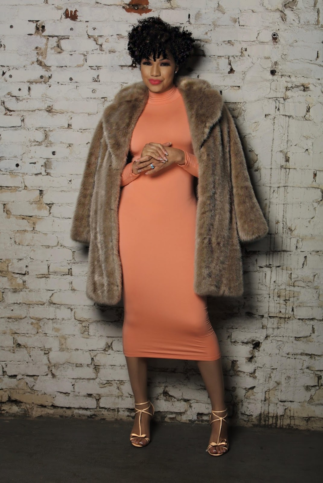 dr eva in a faux fur coat and long fitted peach dress