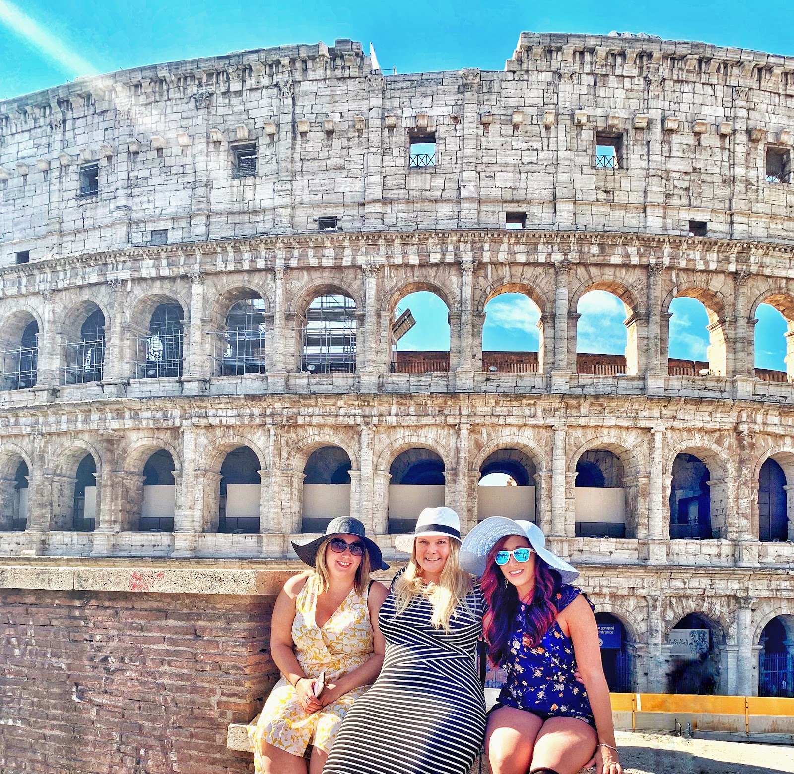 3 women posing in front of the Colosseum in Rome, Italy