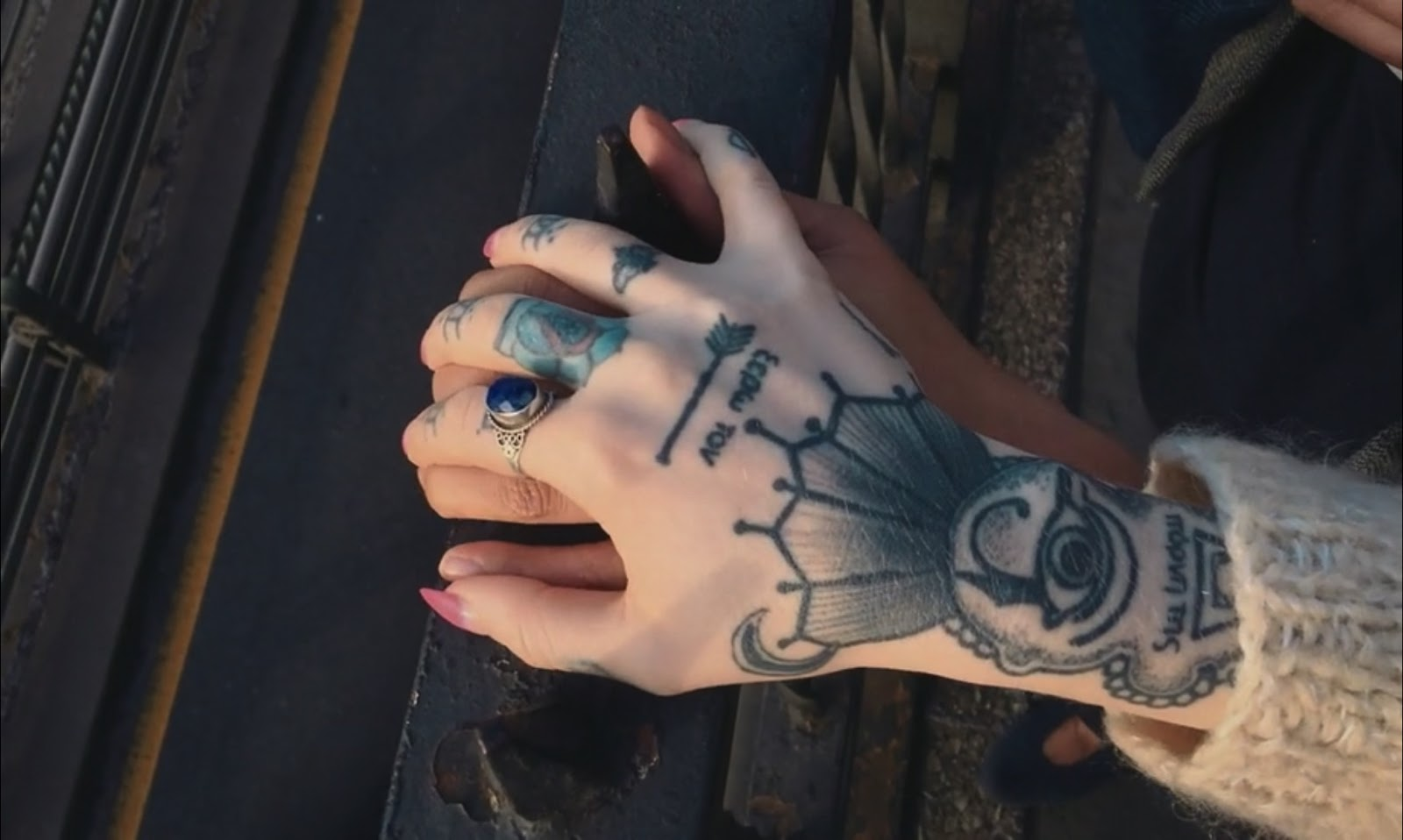 A close-up of two hands on a railing, one resting on top of the other. The hand on top is heavily tattooed and has a ring with a large blue stone in it.