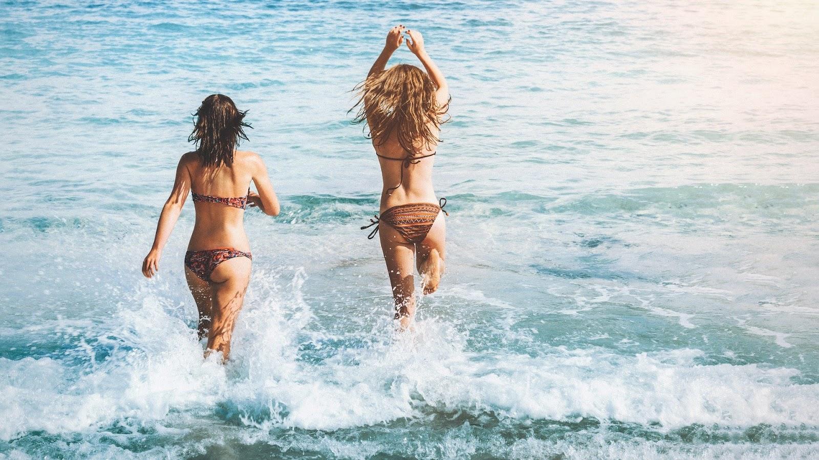 Duas mulheres com tipos de biquínis  entrando no mar.
