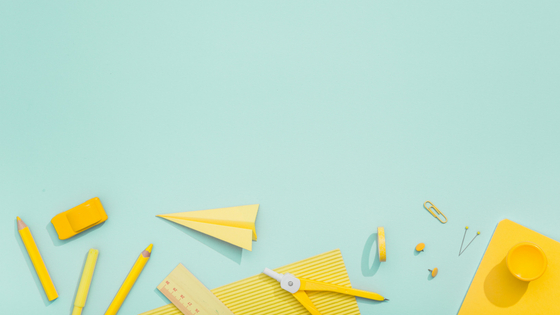 blue background with yellow objects including pencils, paper airplane, paperclip, rulr, compass, eraser, paper