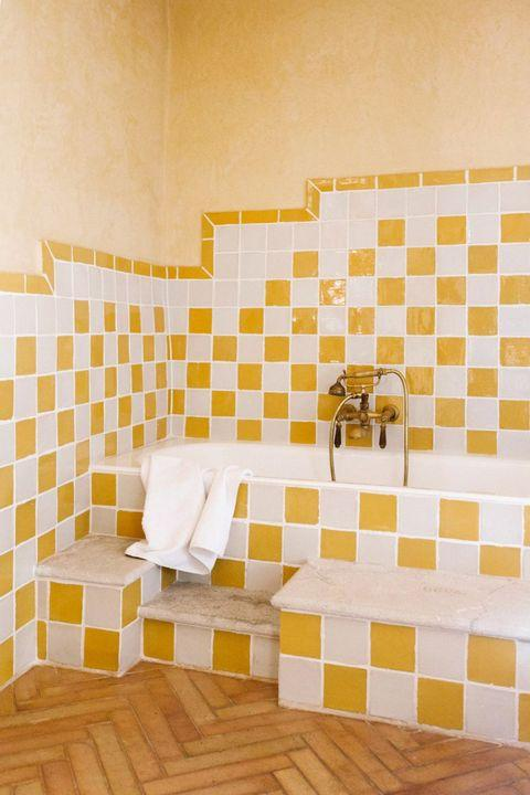 yellow bathroom with tile tub