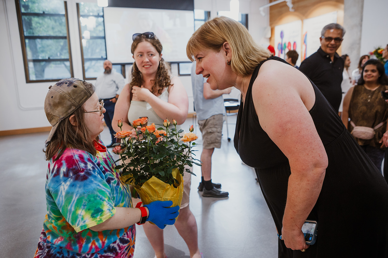 Teresa holds a rose plant given to her by Laurel, an inclusion support teacher in BC. Photo: This Is It Studios.