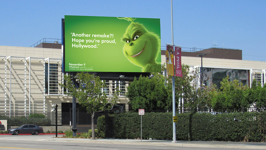 """A green The Grinch Billboard with text """"Another remake?! Hope you're proud Hollywood."""""""