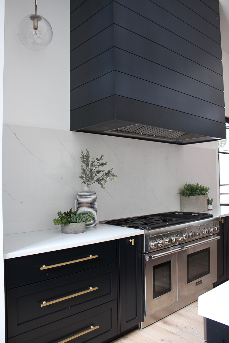 modern kitchen with white backsplash, black shaker cabinets and black paneled range hood