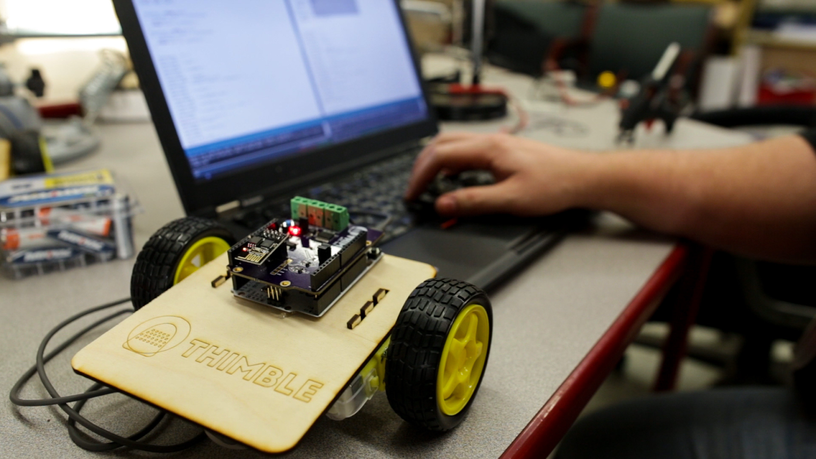 A completed Thimble wifi robot kit sits on a table beside a computer.