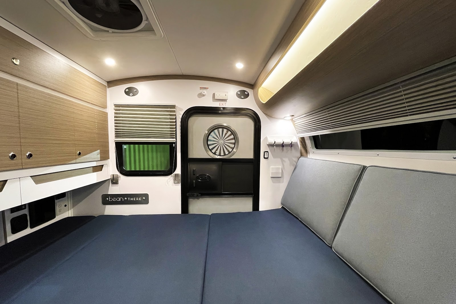 Mean Bean teardrop camper interior with cushions laid out to make a queen size bed.