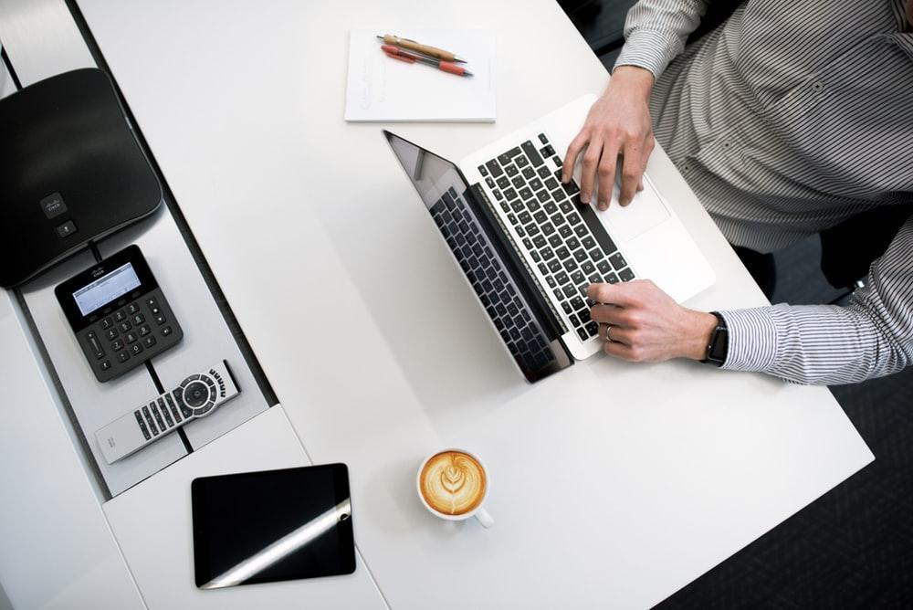 白い木製のテーブルでノートパソコンを使用している人