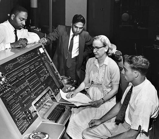 Grace Hopper sentada ao redor de homens em frente a um computador antigo - Mulheres na programação