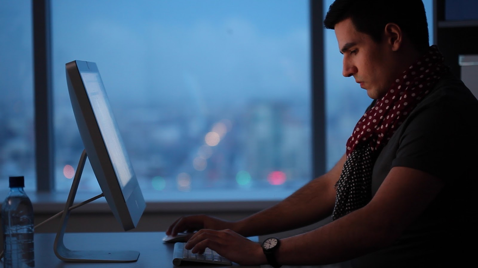 Man with multiple scarves working on laptop