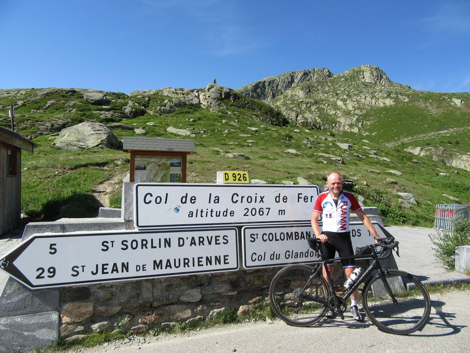 Biking Col de la Croix de Fer, Saint-Jean-de-Maurienne - John Johnson, PJAMM cycling at summit sign