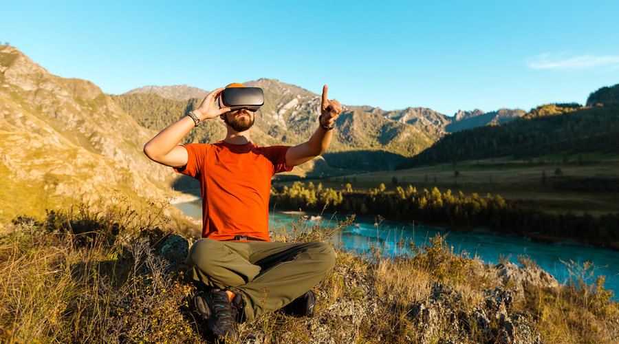 Man in nature next to river and mountains wearing a virtual reality headset