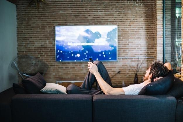 Homem relaxante no sofá em casa