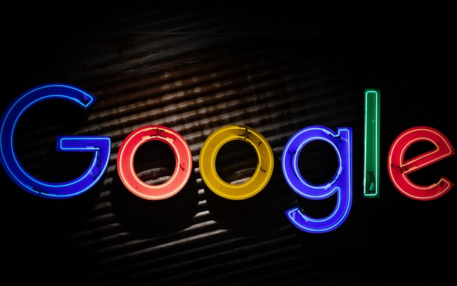 A Google logo with neon lights with a black and brown background.