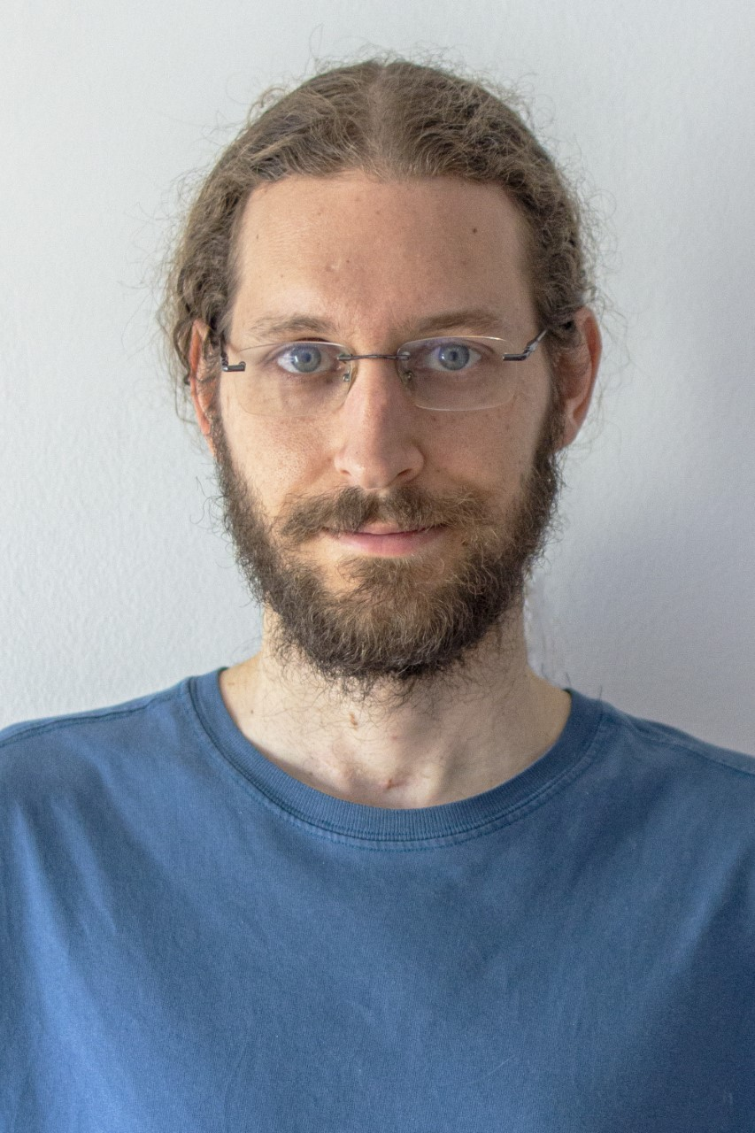 A person with glasses and a beard is standing in front of a white wall