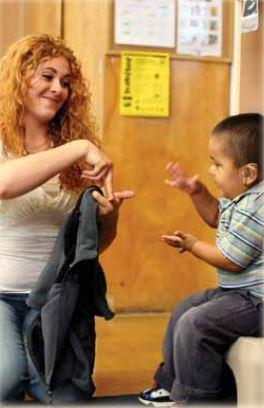An instructor speaking to a child in sign language