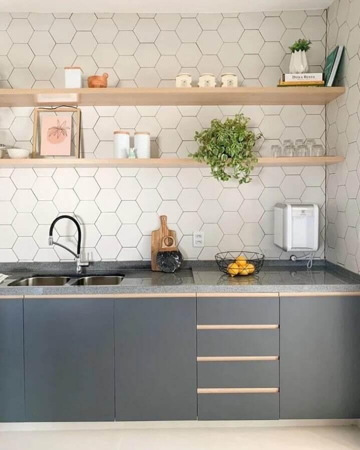 Cozinha com armário cinza, bancada da pia de mármore, revestimento hexagonal branca na parede da pia e prateleiras de madeira com utensílios de cozinha.