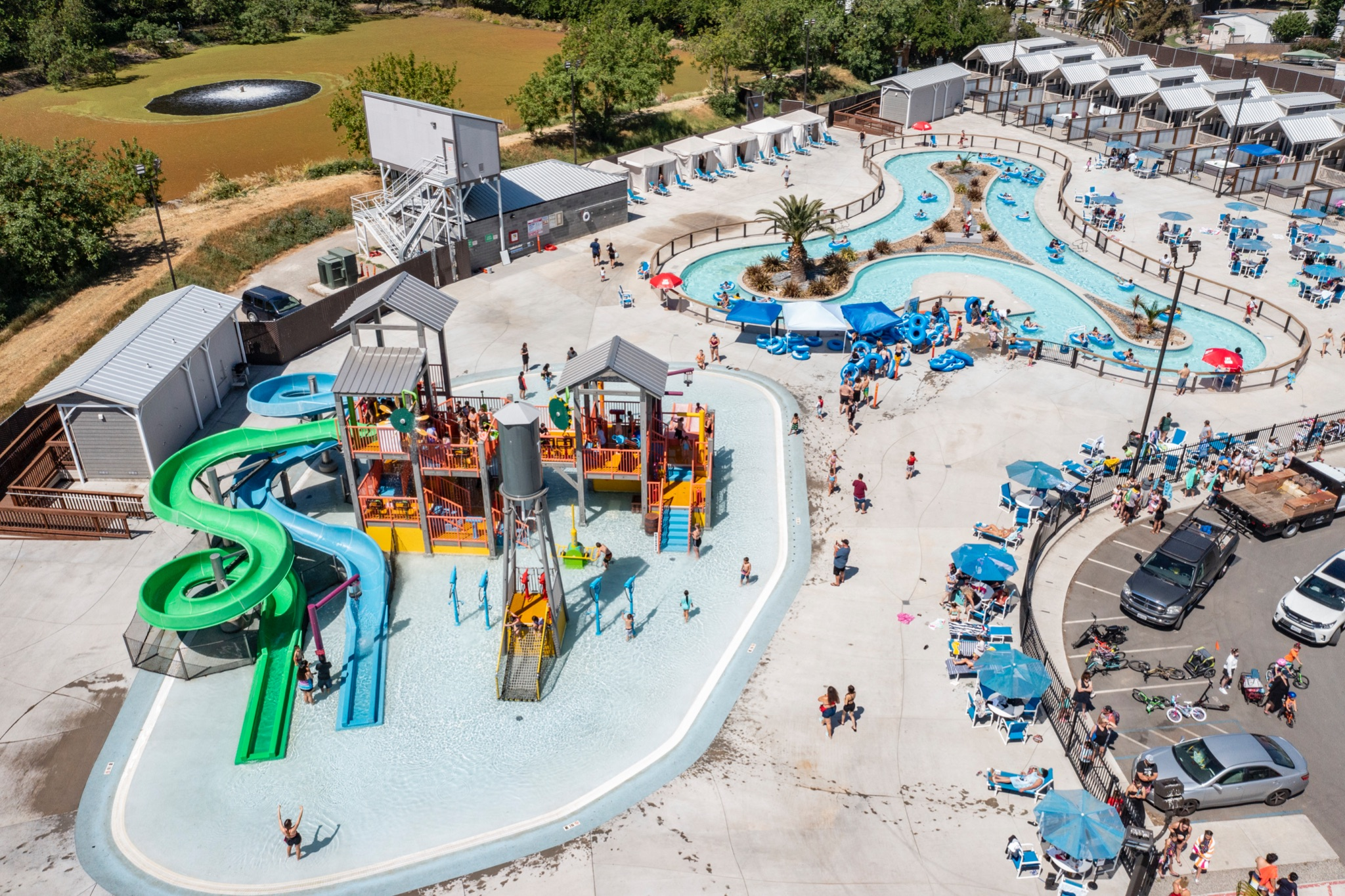 Ariel view of the pool and water zone at campground with cabins in the background.