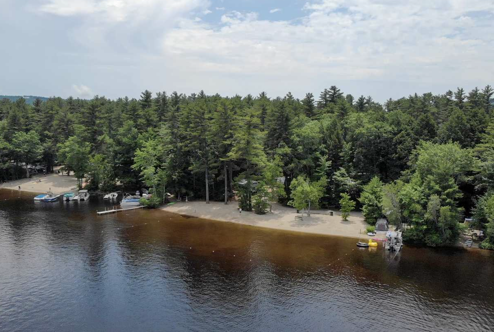 Aerial view of lake at Yogi Bear campground with woods in background