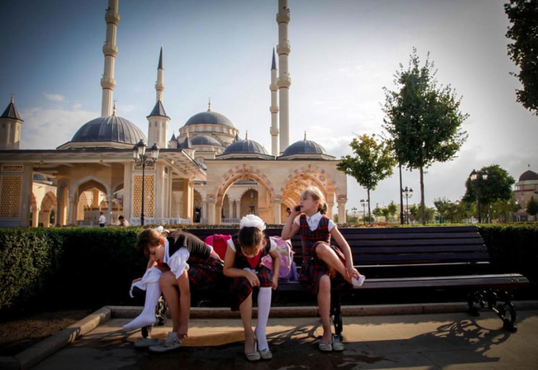 Photo de trois petites filles en tenues d'écolières assises sur un banc