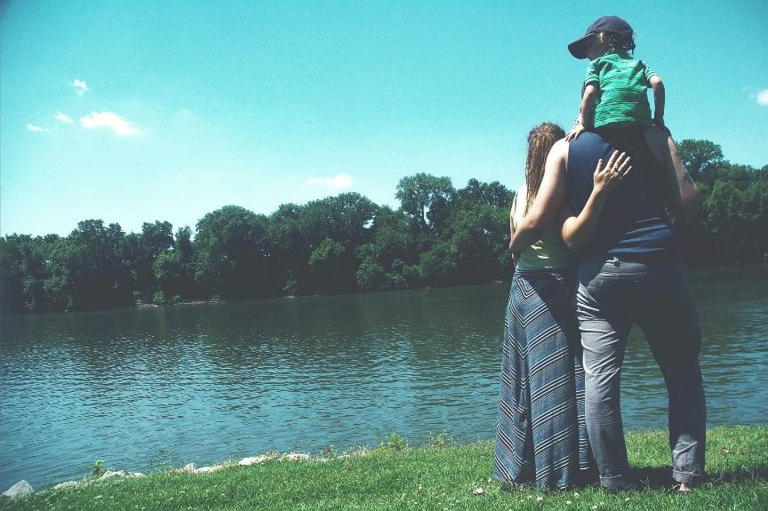 A family of three standing on the grassy shores of a lake looking towards the water.