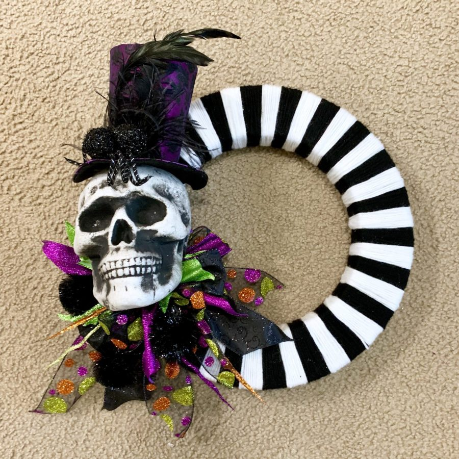 Gluing the top hat on the Halloween wreath.