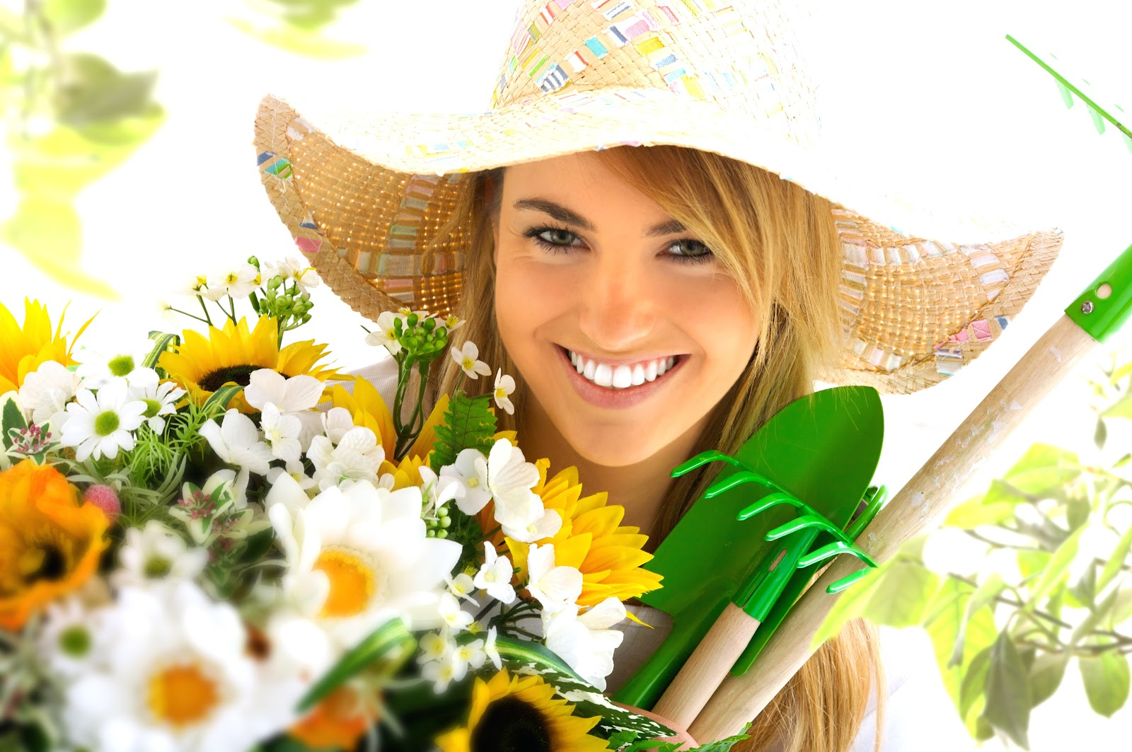 A woman smiling with plants and gardening tools