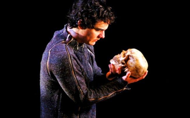 """#PraCegoVer audiodescrição resumida: Fotografia do espetáculo """"Hamlet"""". Fundo preto. Ao centro, o ator Wagner Moura, homem de pele branca, olhos e cabelos pretos. Ele está de lado, segurando um crânio humano com ambas as mãos, enquanto olha para o crânio."""