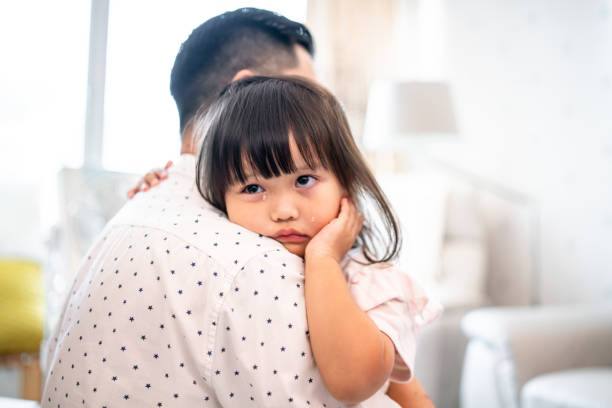 father consoling crying daughter