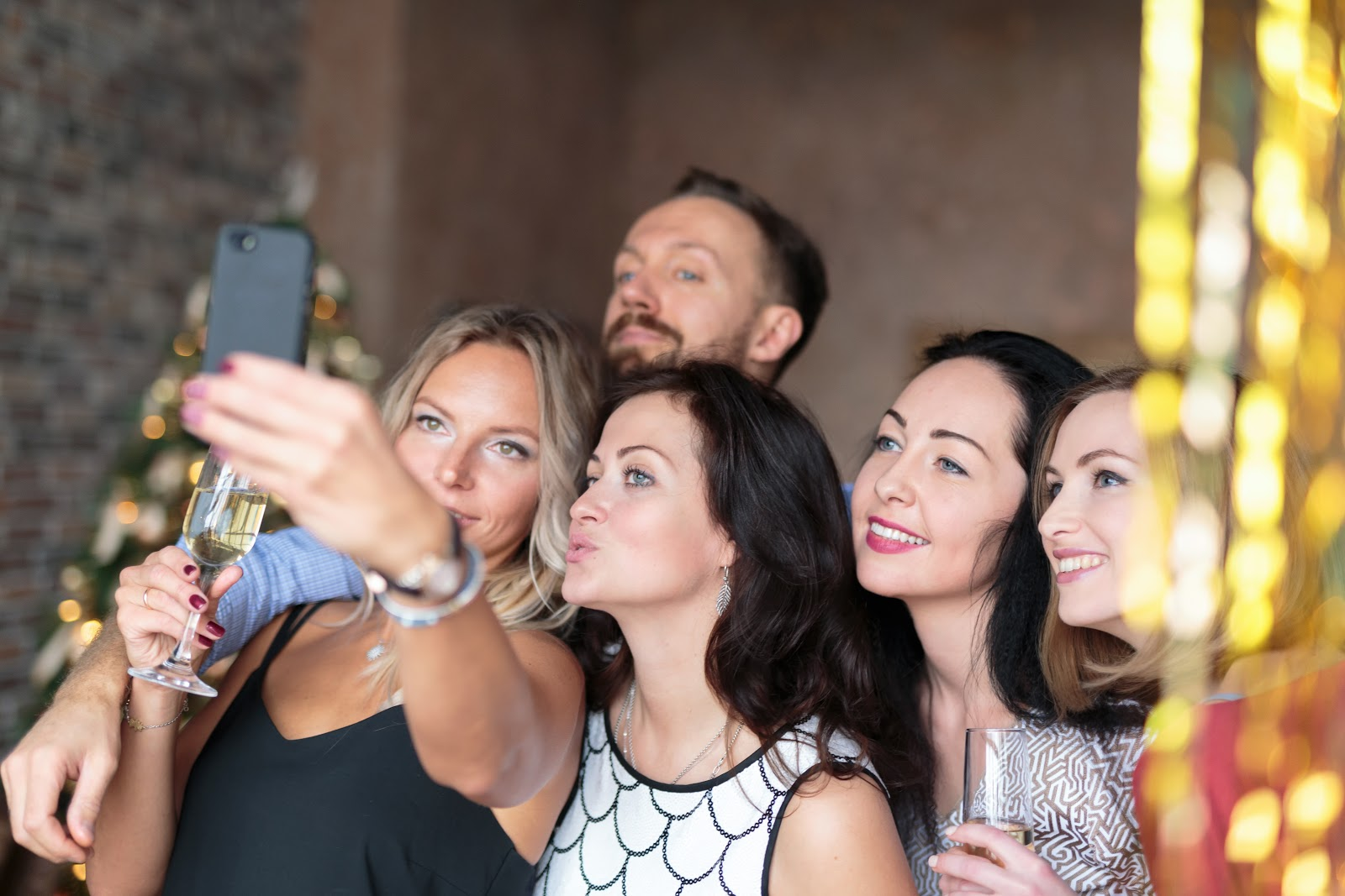 A group of people taking pictures at a party or wedding, friends