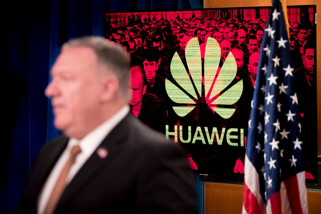 A monitor displays the logo for Huawei behind Secretary of State Mike Pompeo as he speaks during a news conference at the State Department in Washington, D.C. on July 15, 2020. Krach and Pompeo's heavy blows against Huawei have left the CCP's telecom giant in a state like a withering flower.