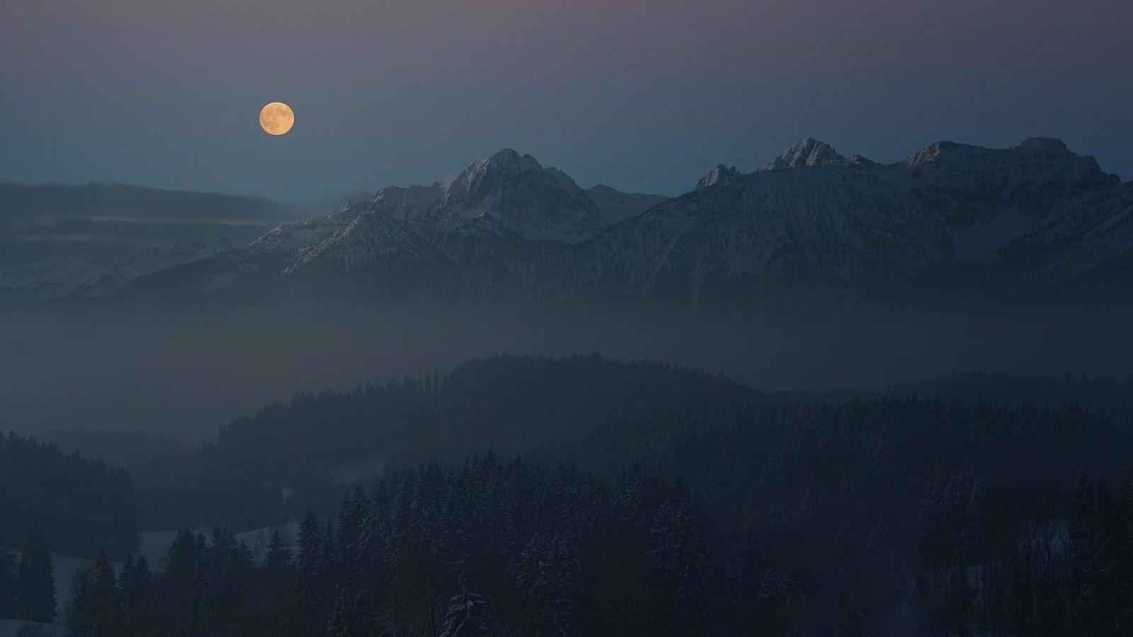 large mountain range with yellow moon