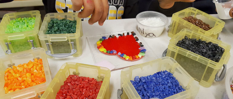 A child selects pieces of glass to arrange into a heart shaped fused valentine.