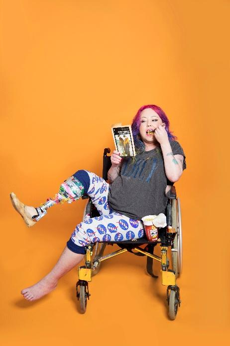Image description: Jackie Hagan is sat in her manual wheelchair with her legs to the side, so that her prosthesis is on full display for the viewer. She is eating a pot noodle whilst reading the paperback book, 'Love on the Dole'. Jackie has vibrant pink and purple hair, and is casually dressed in a dark grey T-shirt with white and blue patterned leggings, which are cropped at the knees. The entire background is orange.