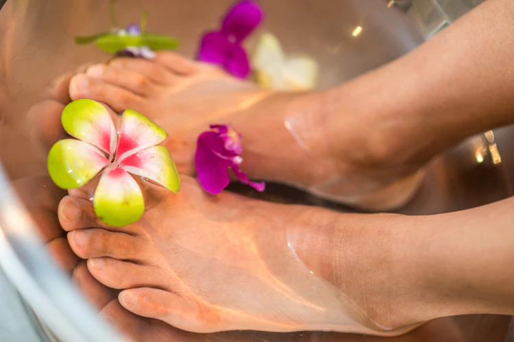 Feet in a bowl of water with flowers