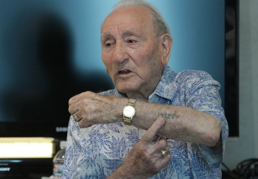 Holocaust survivor Joseph Alexander shows his identification tattoo from Auschwitz