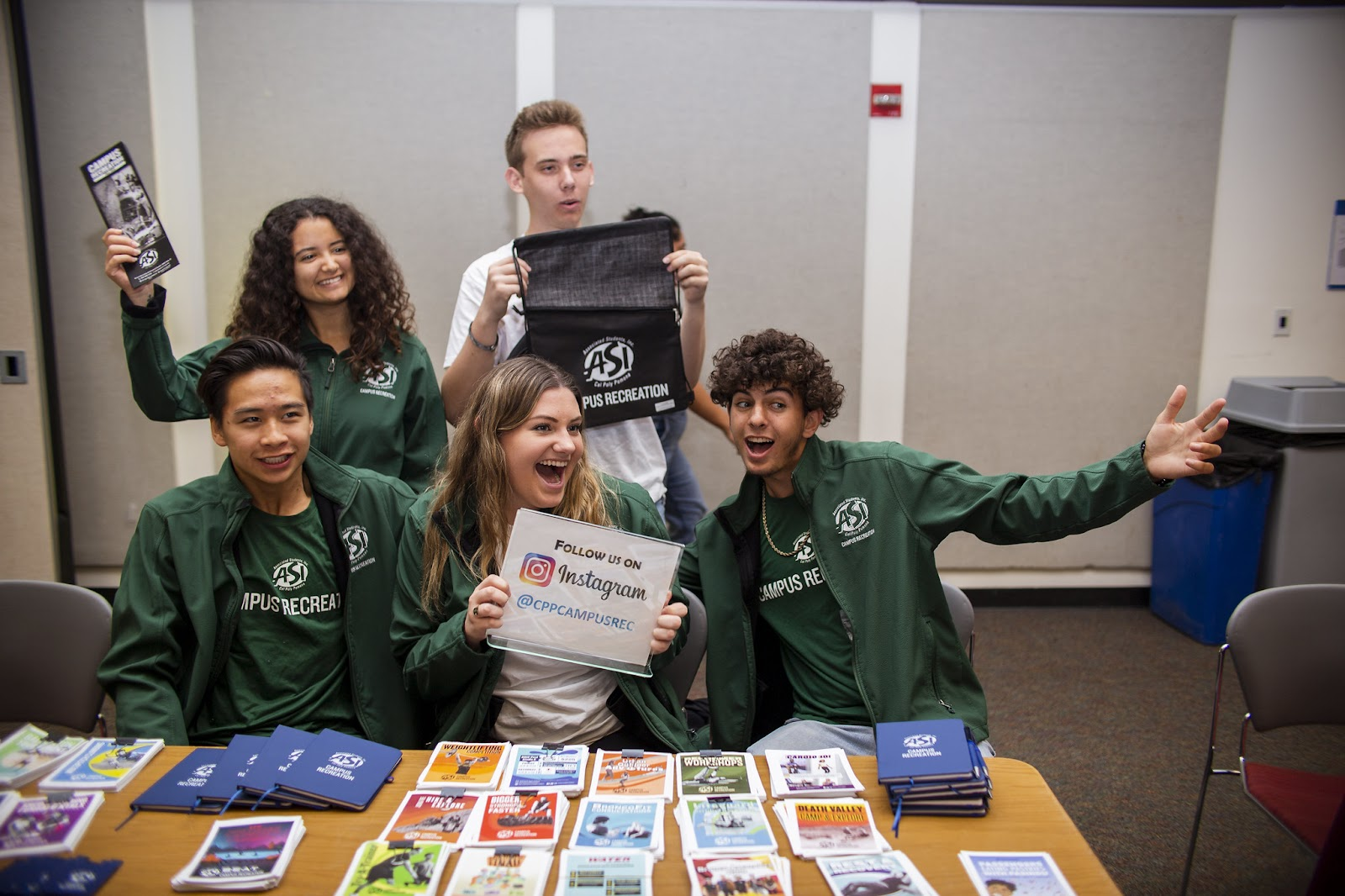 Students holding Campus Rec merchandise and posing for picture