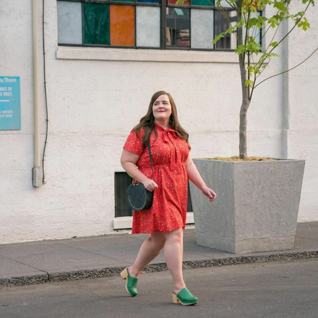 Annie in Shrill.  Image: Annie is mid-crossing the street in this photo. She wears mint green clog, a coral flowery short-sleeved dress that is cinched at the waist and ties into a tight collar around her neck. She wears a forest green purse, and looks casually to the left as she crosses the street.