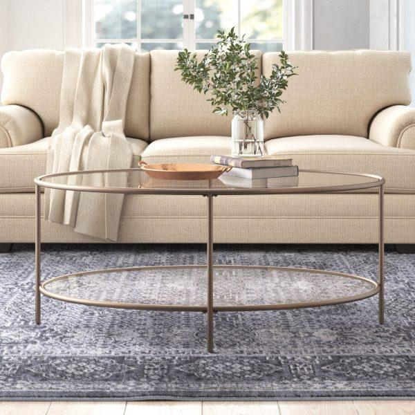 http://cdn.home-designing.com/wp-content/uploads/2021/04/oval-glass-top-coffee-table-with-storage-shelf-antique-silver-frame-transitional-living-room-furniture-subtle-glam-look-600x600.jpg