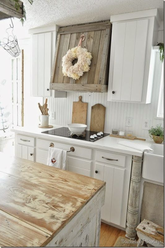 Distressed vintage farmhouse kitchen with white panel cabinets, wood range hood, distressed butcher block island, white countertops and shiplap backsplash. Small farmhouse cabinets are paired with gold hardware