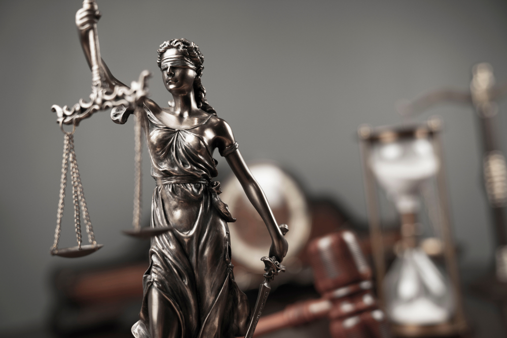 A lady justice statue with an hourglass and a gavel in the background