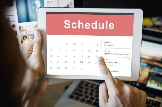 person holding a tablet, opening their schedule