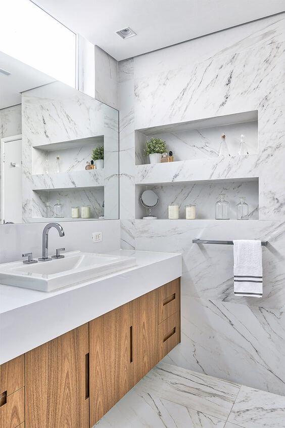 banheiro com revestimentos marmorizado na parede e piso, armário amadeirado com bancada branca e espelho retangular.