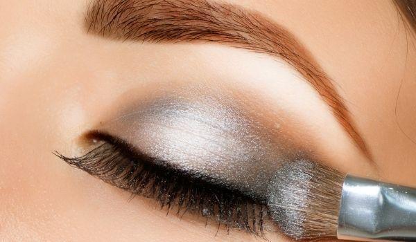 close up shot of a brush applying silver eyeshadow on eye