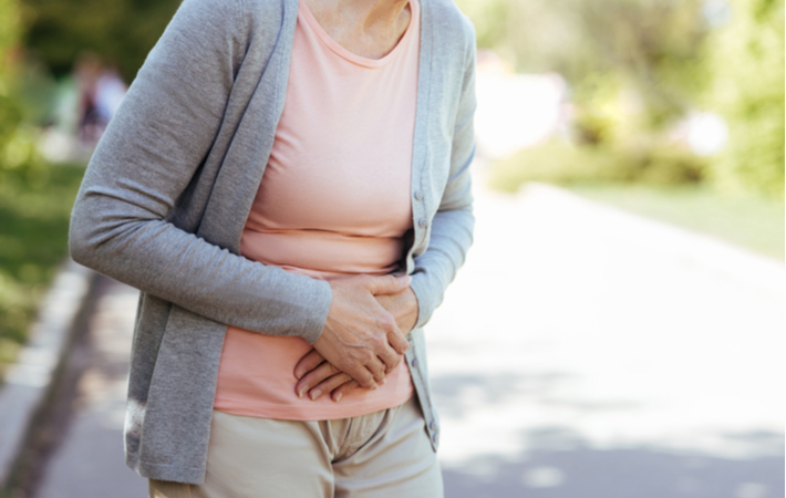 older woman holds stomach in pain while outdoors