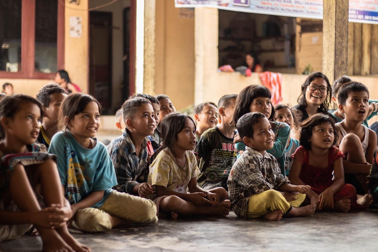 Grupo de pessoas sentadas no chão  Descrição gerada automaticamente com confiança média