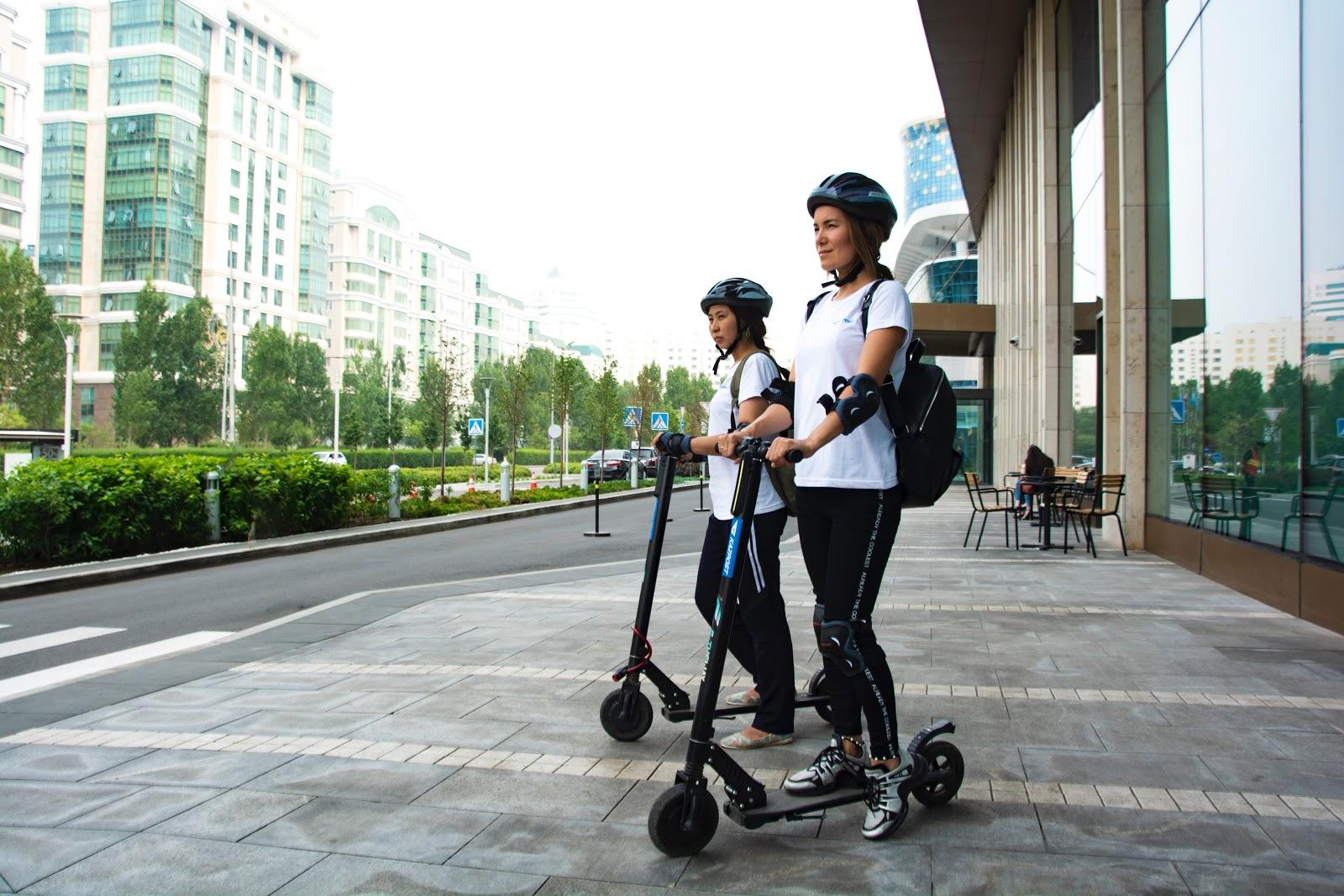 Due ragazze con il casco sono ferme sul monopattino elettico