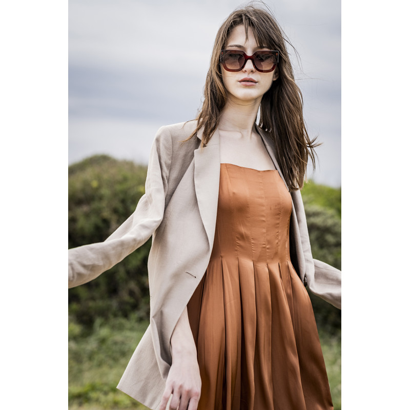 White woman wearing brown dress with pleated bodice and tan blazer on top
