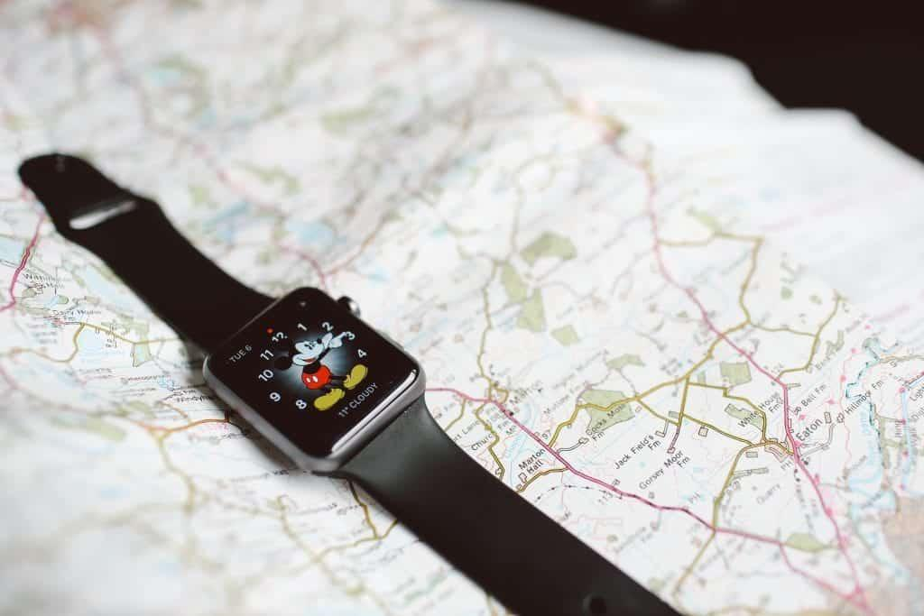 Photo shows a map with an apple watch with Mickey Mouse on it, representing how Heyday Travel Company has Disney Travel Agents That Save You TIme and Hassle. Photo by Lilly Rum on Unsplash.
