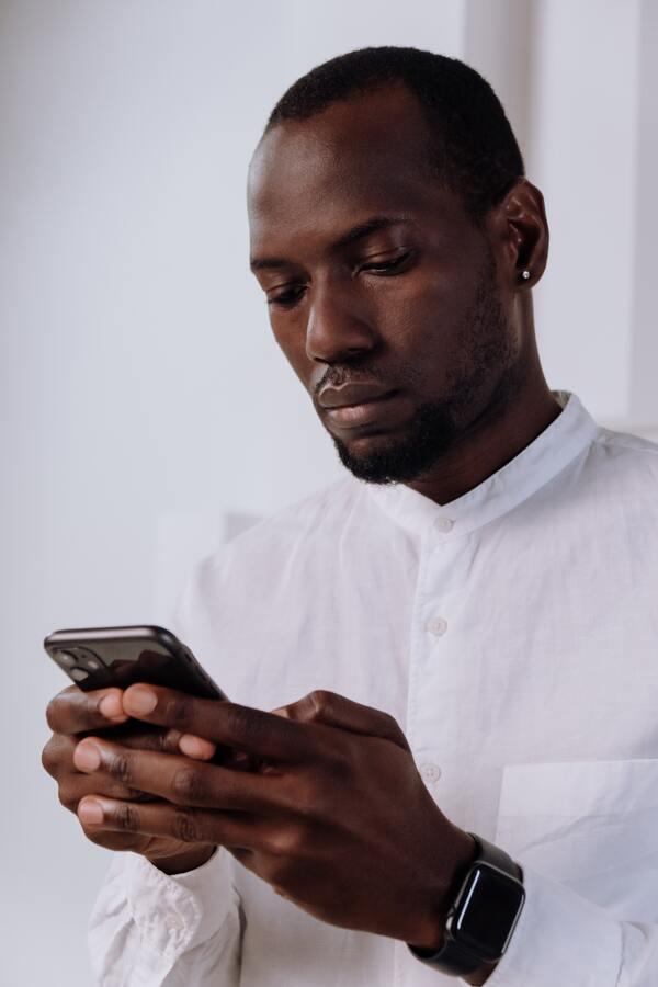 homem negro sentado e mexendo no celular